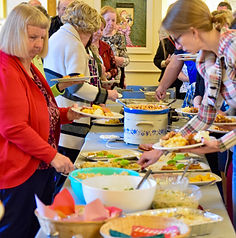 Church members sample favourite dishes at a church potluck dinner.