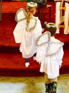 Young Sunday school aged angels carry microphones prepared to narrate the Christmas pageant.