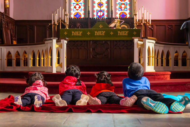 Four children play on blanket at the front of the worship space near the altar of St. John's Thorold