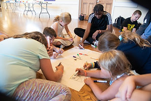 Children and youth sharing a drawing activity on banner paper.
