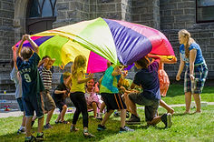 Children gather under a parachute outside in the church yard.