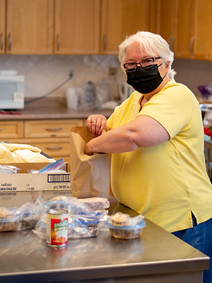 A volunteer packing the Community Meal Programme take-away lunches.
