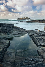 Godrevy Lighthouse on the North Coast of Cornwall with a cloudy blue sky a reflection in the rock pool