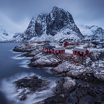 A view over Hamnøy in Lofoten, Norway at dusk with slow moving clouds and soft seas, the little red fishing rorbuer on the waters edge