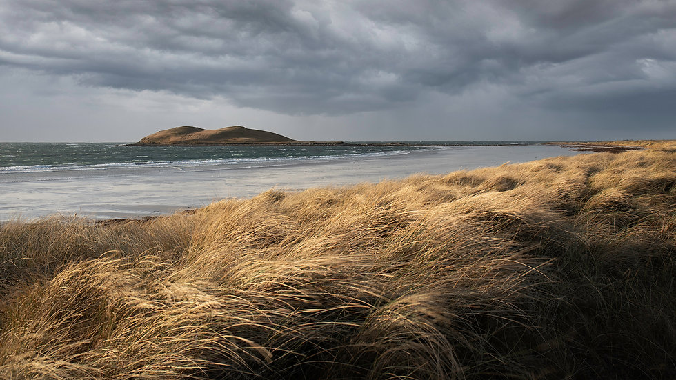 Island Storm passing on the Isle of South Uist, standing on the shores watching the storm clouds rolling past as the light illuminates the machair grasses of the Outer Hebrides