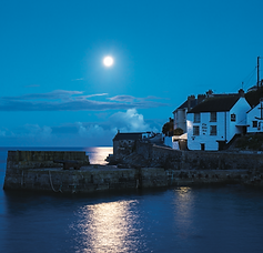 Moonlight shines down on the harbour at Porthleven Cornwall during pre dawn in the summer.