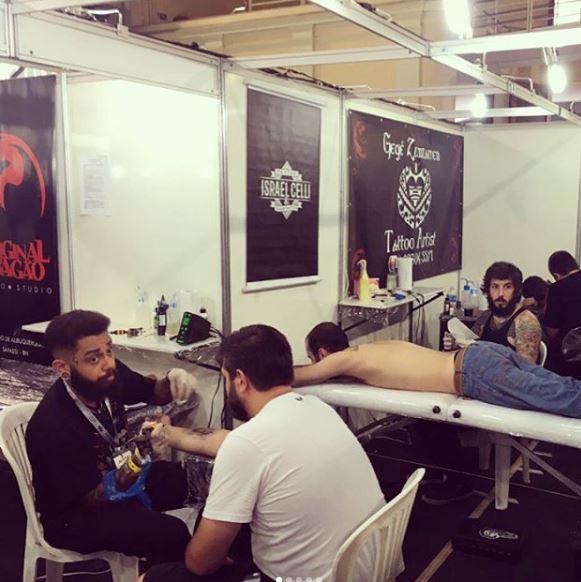 Tulio e Israel tatuando durante o evento.