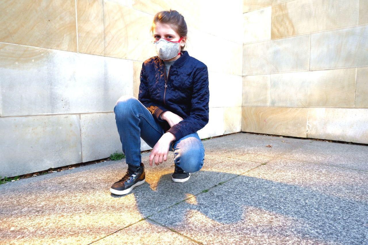 Anders als die weißen Krankenhausmasken fällt diese Maske kaum auf und sieht gut aus