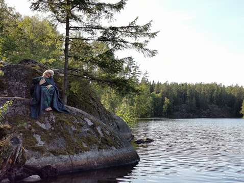 Girl on a rock with 'Forest' bedding by lake