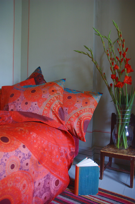 A room with 'Rainbow' red bed and flowers
