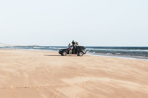 Small group riding car down the coast of