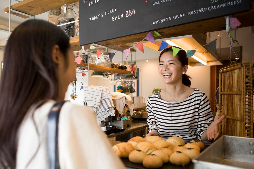 Hymyilevä ihminen edessään leivonnaisia ja toinen ihminen.