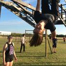 girl upside down on monkey bars
