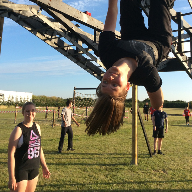 girl upside down on monkey bars