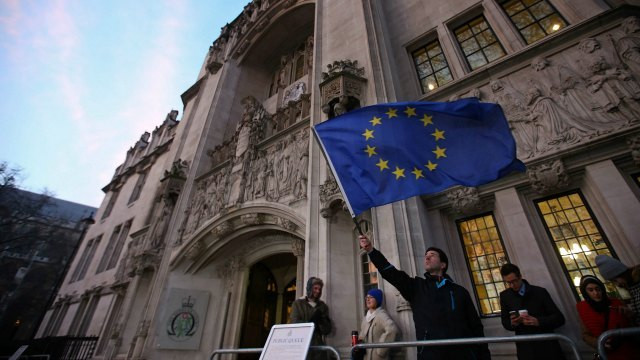 An anti-Brexit protester waves an EU flag outside the UK Supreme Court building in London
