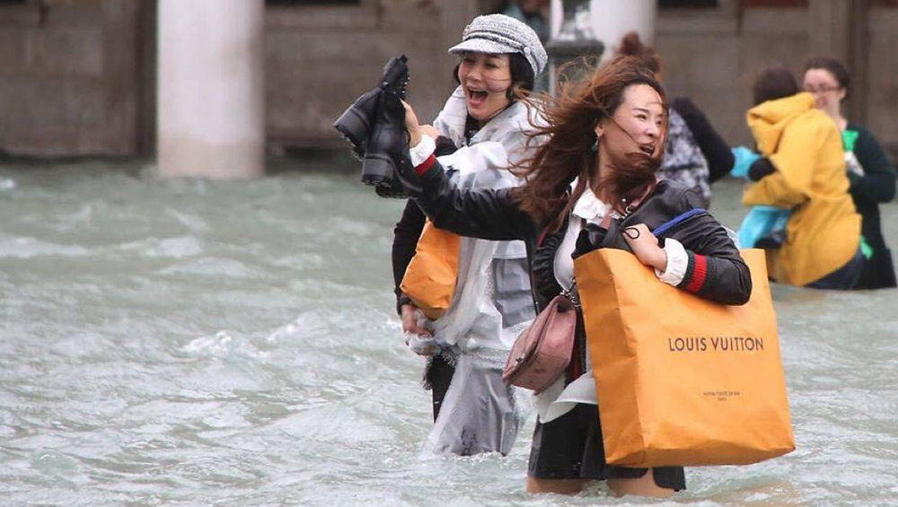 Two women wade through the floodwaters of St Marks Square in Venice holding large Louis Vuitton shopping bags