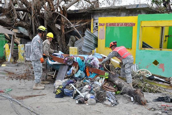 Puerto Rico National Guard Soldiers, along with volunteers of the Puerto Rico State Guard, work together to clear road debris at Punta Santiago in Humacao, Puerto Rico on Sept. 27, 2017. (Photo by Spc. Hamiel Irizarry)