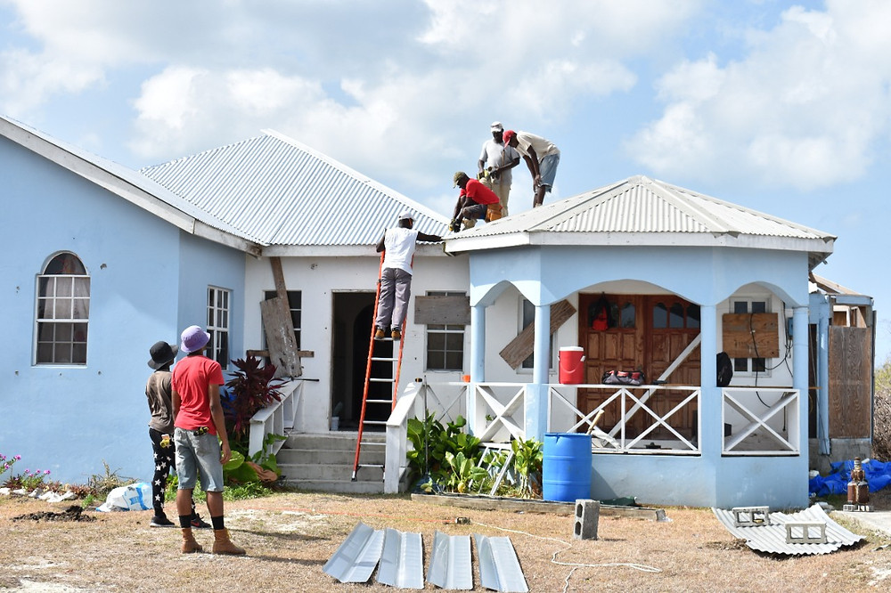 Contractors re-roofing home damaged by Irma on island of Barbuda as part of UN relief projected sponsored by China.