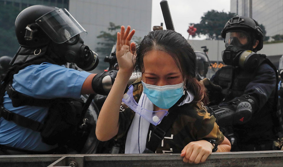 A protester is confronted by riot police during a massive demonstration outside the Legislative Council in Hong Kong on Wednesday, June 12, 2019. Protests against a proposed bill that would allow extraditions to the rest of China continue in Hong Kong, despite the city's government withdrawing the proposed measure. | Kin Cheung / AP