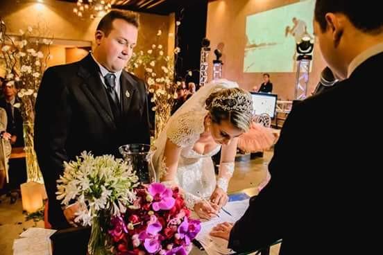 Noivas assinando documento do cartório durante a cerimônia de casamento realizada por um cerimonialista de casamento