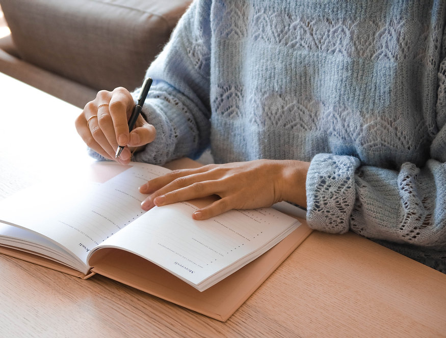 woman in white and gray sweater writing on white paper_edited.jpg