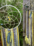 """10"""" on metal hoop wrapped in yarn, knotted web, beads, faux eucalyptus, ribbons, yarns and feathers."""