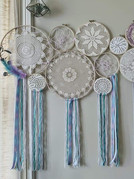 Large collage, wood hoops with vintage doilies and knotted web, yarns, ribbons, faux eucalyptus and feathers.