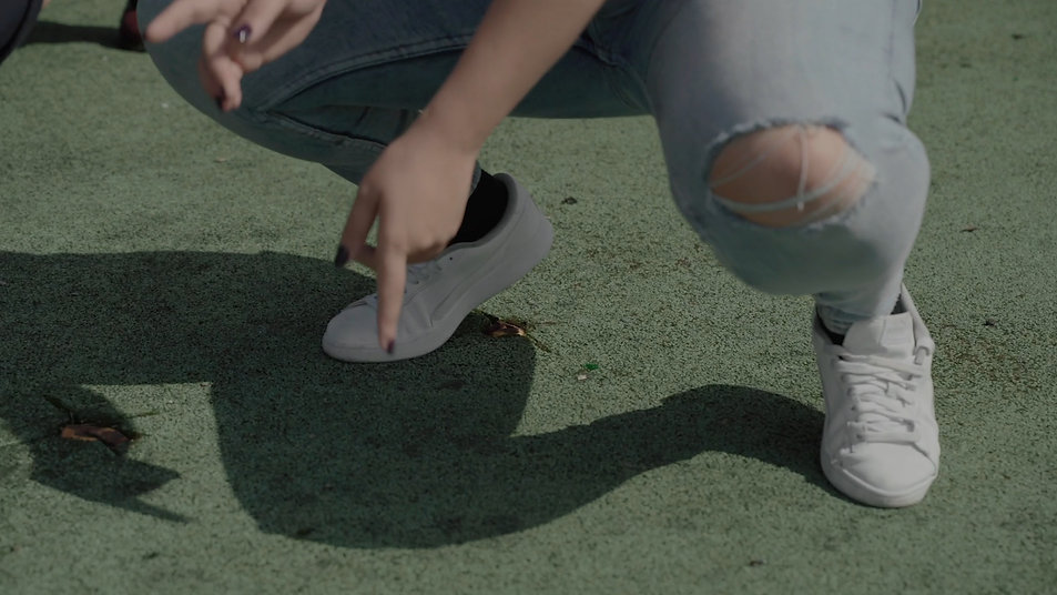 Close up of someones legs squatted down dancing in the middle of a playground.