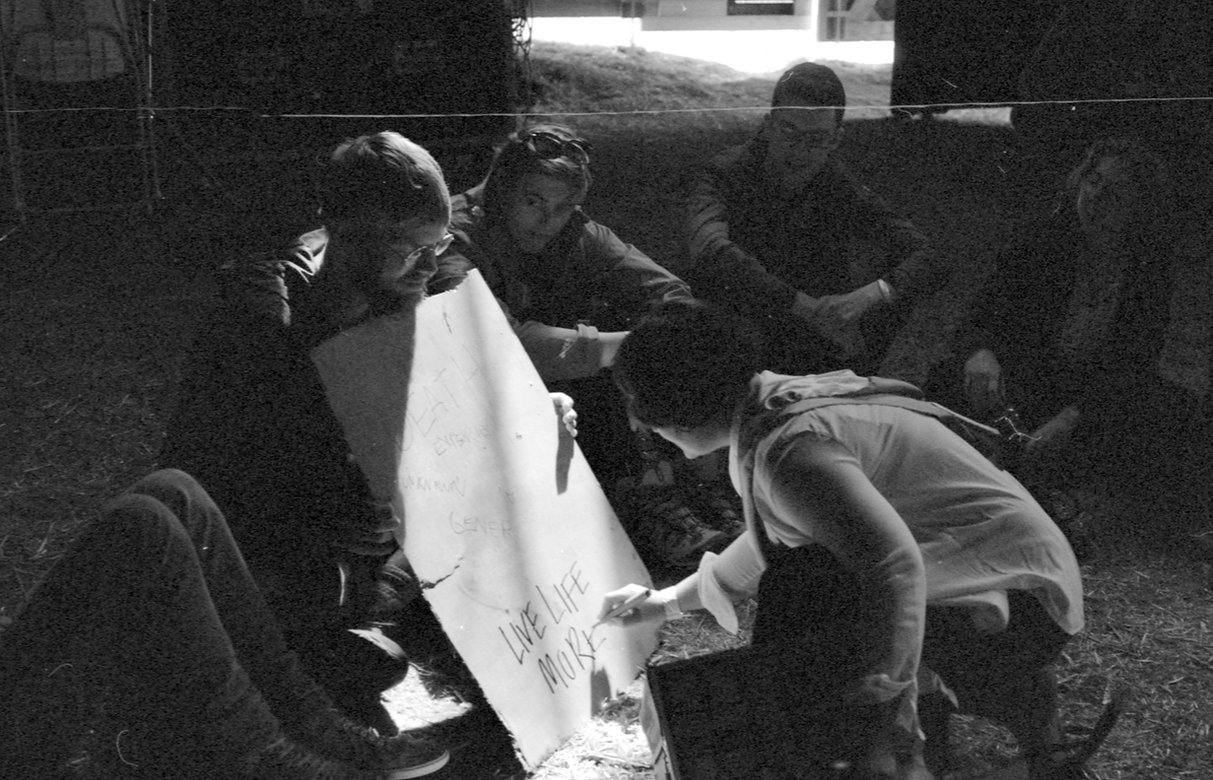 Image Description: A black and white photoof a group of people sitting outside, Kerri writes 'LIVE LIFE MORE' on a board that is held up by another member of the group.
