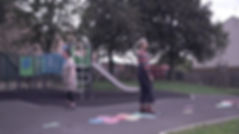 Two people stand in a playground with their backs to each other a little distane a part. Behind them there is a slide and climbing frame, the ground has colourful hopscotch tiles.