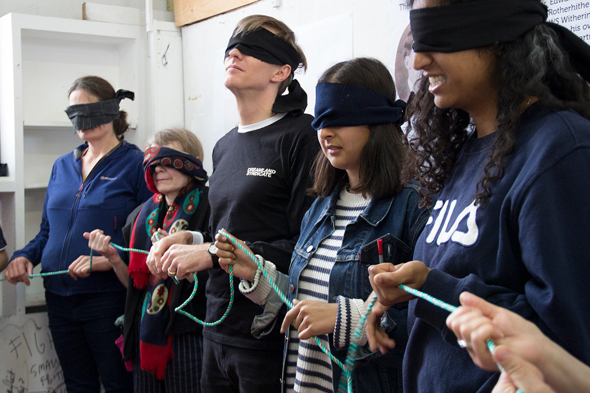 Image Description: A group of peole stand in a line, blindfolded, holding a piece of rope, together.