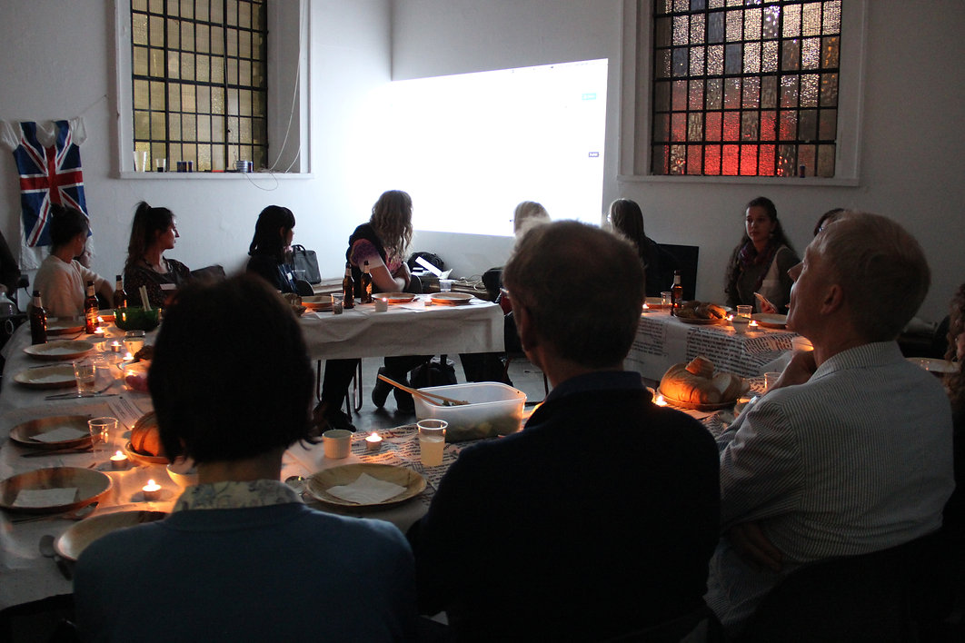 Image Description: Abot twenty  people sit around a square arrangement of tables, lit by candles, preparing to have dinner.