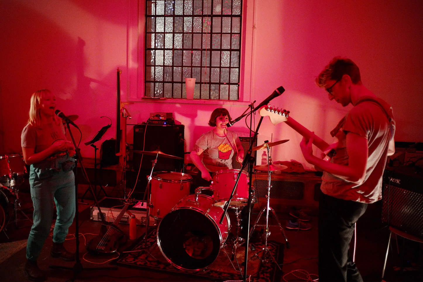 Image Description: A room lit with red lighting, showing Sophie on vocals, Kerri on drums, and Giles playing guitar.