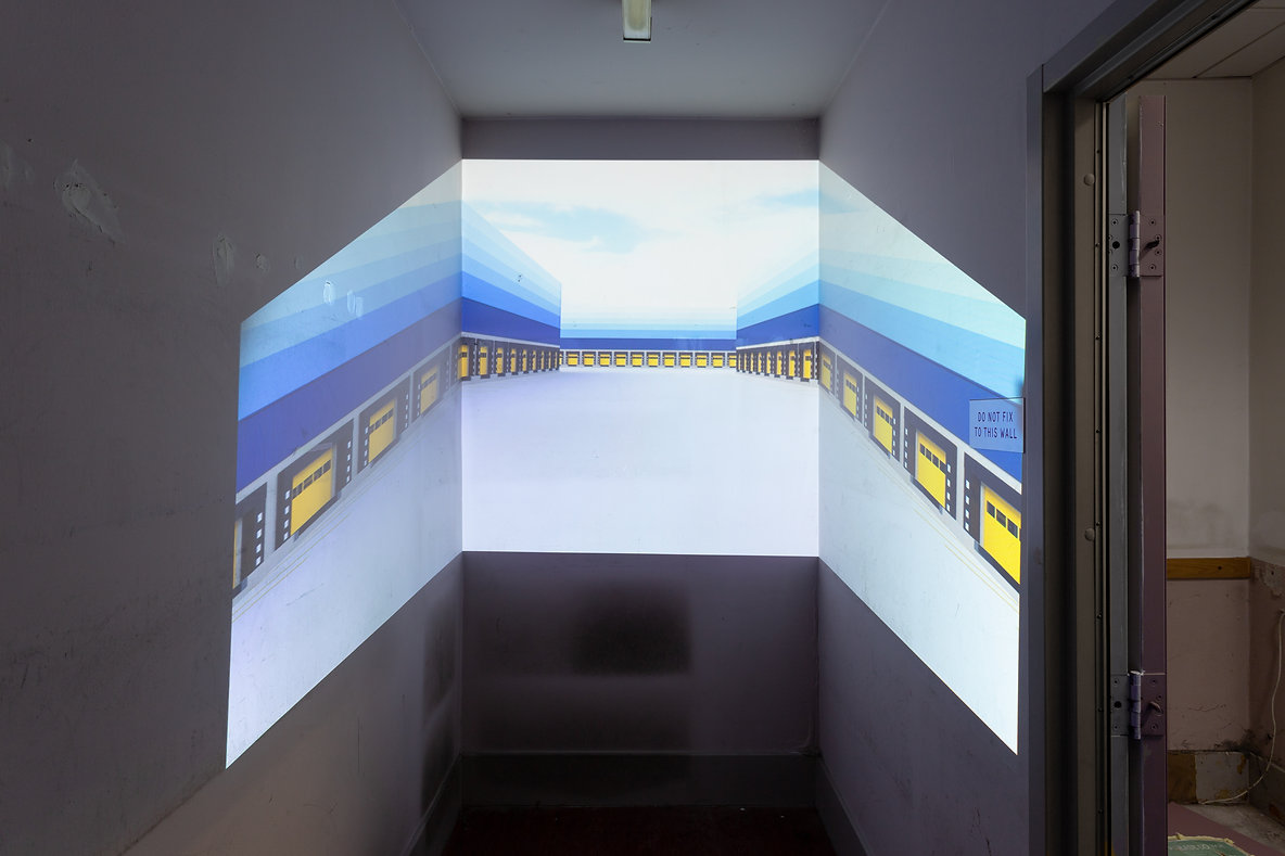 Photo of a projection in a slim wall with the projection covering the end of the room and part of the walls either side. The image shows blue and yellow amazon style warehouses that go on for infinity