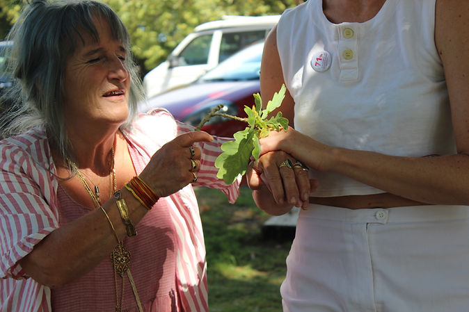 Image Description: A woman clasps another woman's hand between her own, whilst clutching a sprig of leaves.