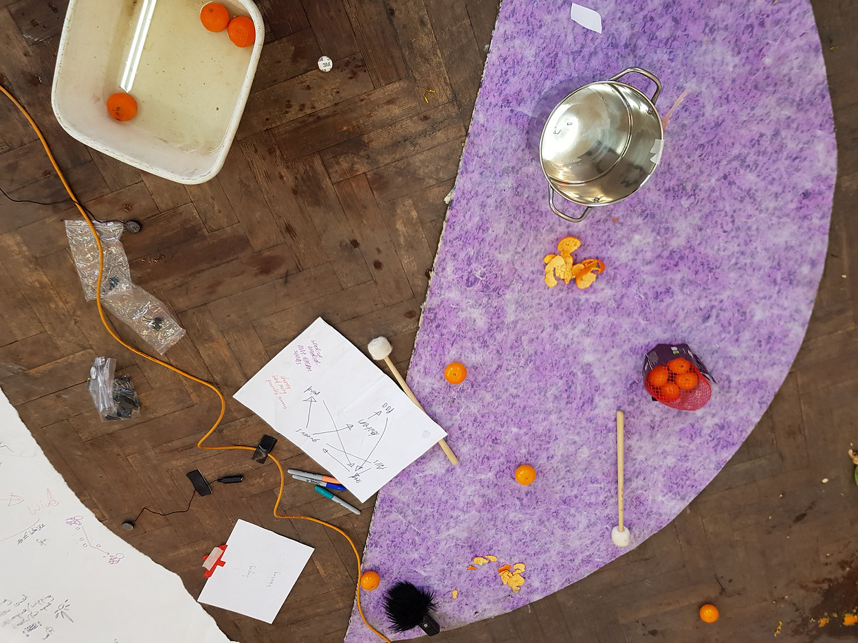 Image Description: On the wooden floor lies satsuma peel, satsumas in a tub of water, Sharpies, a curling wire, a saucepan and drumsticks, sat on top of a lilac textured material.
