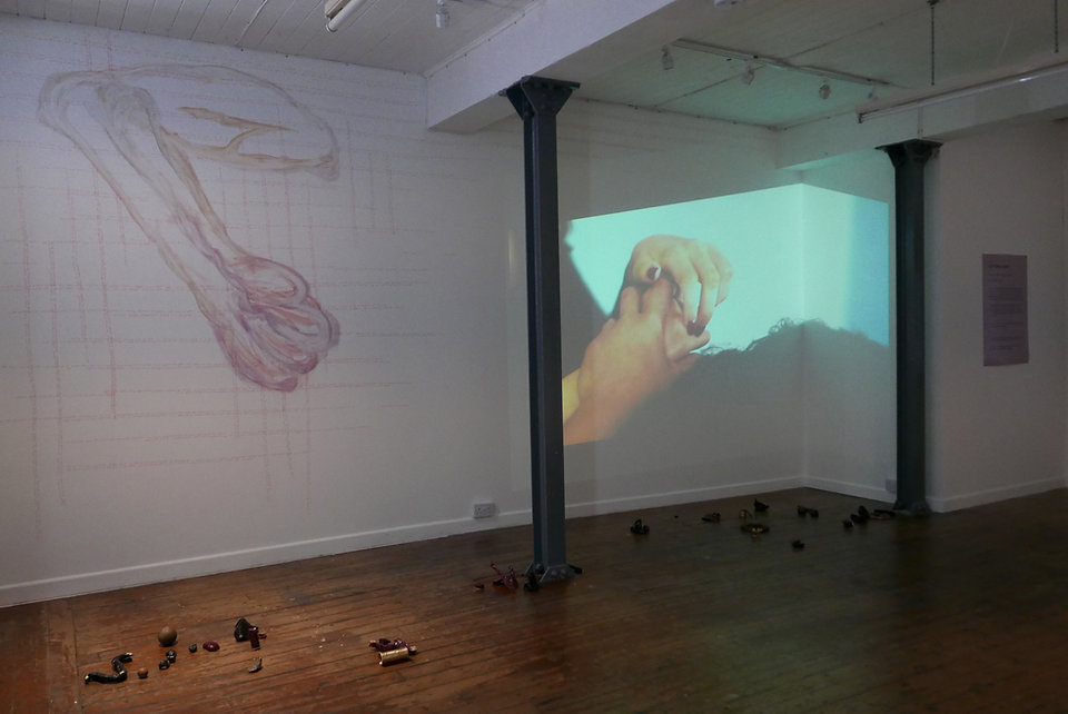 Installation: a large drawing covers the wall alongside a projection of hands holdng a sculpture, as other ceramic sculptures are scattered along the floor