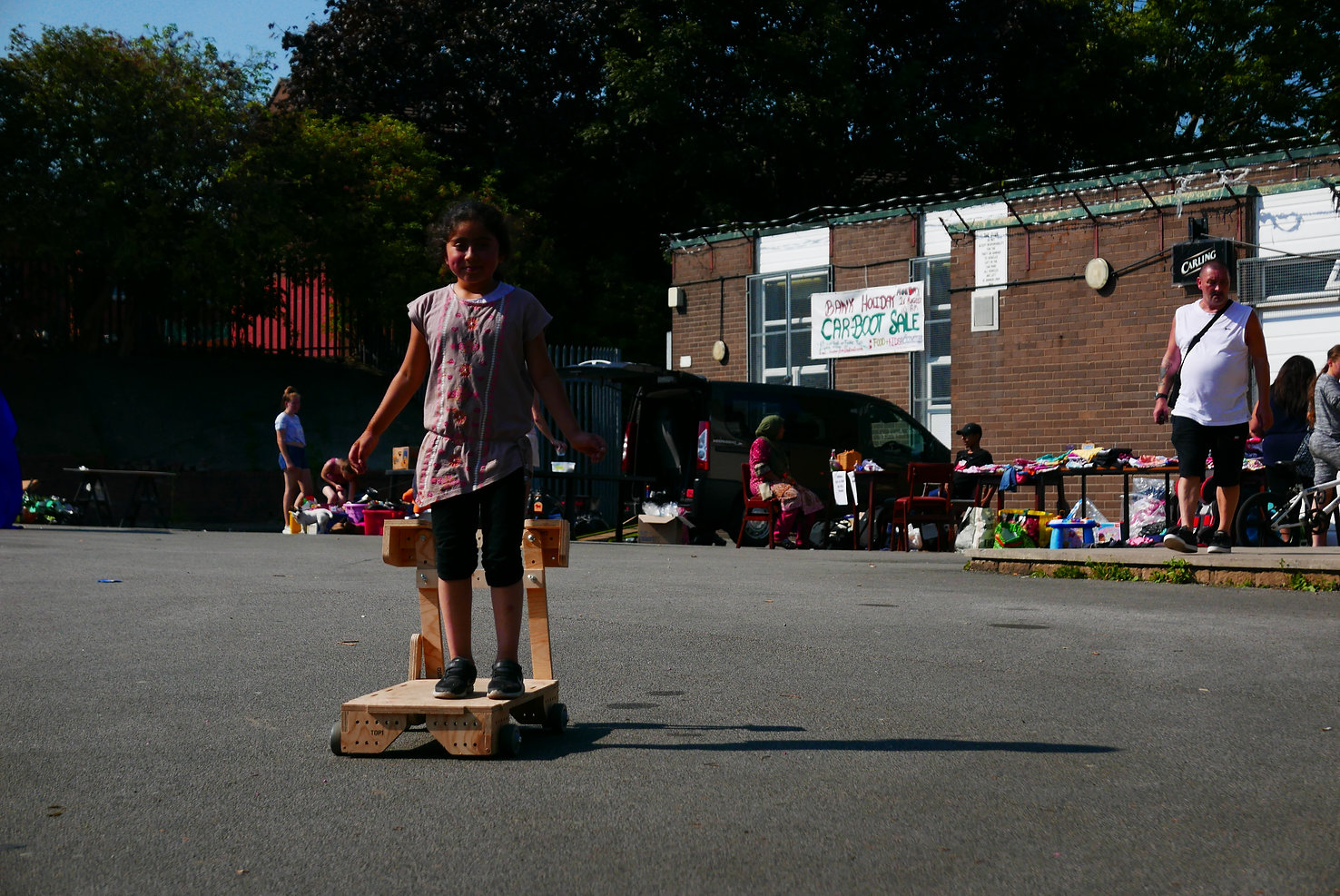 Photograph of a young person standing on a wooden wheeled go-cart they have built, in the middle of a car park with a car boot sale going on in the background.