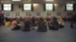 A group of people of various ages sit on the floor in a circle in the hall at a working men's club talking. The floor has soft judo matts on it, windows let sun in and there are framed black and white pictures on the walls