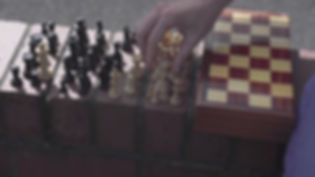 Close up of someone's hand moving a chess piece, there are all the chess pieces laid out on the side of a brick wall with the box next to them.
