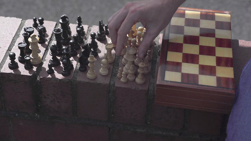 A hand moves a chess piece balanced on a brick wall
