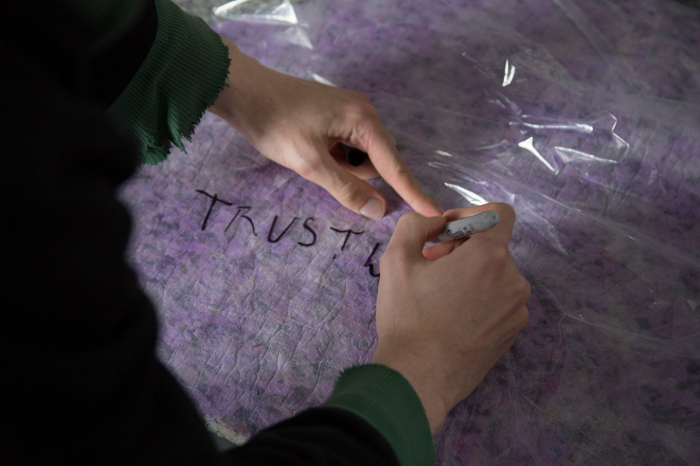 Image Description: Someone writes 'TRUST' in black sharpie on a large sheet of plastic.