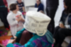 Image Descriptions: Group sits around one mperson who is wearing a soft cloth basket on their head. The group is writing on it. One side reads 'have to start again, miss family.'