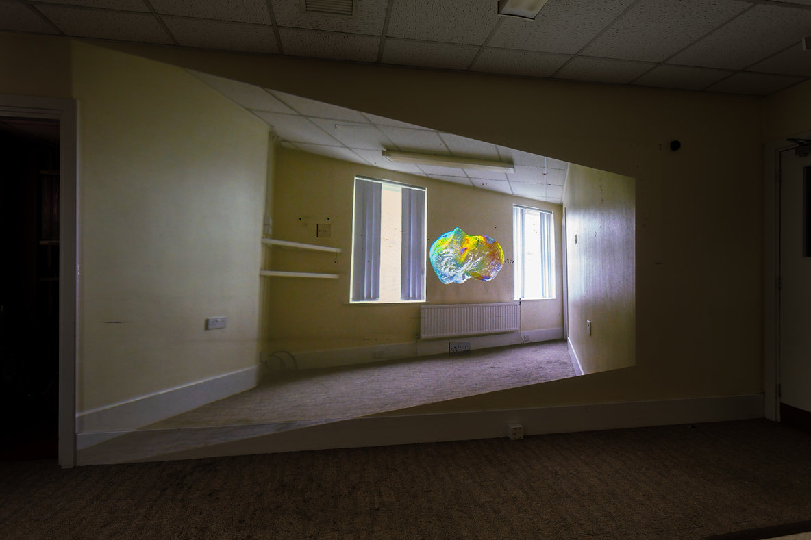 Photo of a projection, in the projection a video of an office room with 2 windows, apearing to float in the middle is a blobby, semi translucent multicoloured form