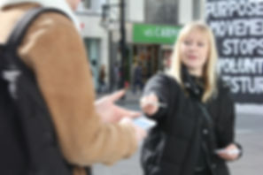 Image Description: Sophie handing a card to someone else on the street, in front of the placard..