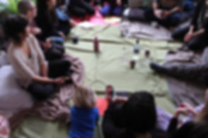 Image Description: A group of people sitting on throws and cushions with a vodka bottle and a circle of glasses around it in the centre.