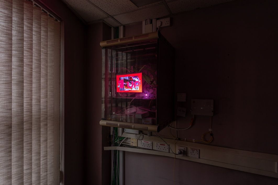 Photo of a glass cabinet full of wires and cables, with a red animation projected onto the glass that reads '1up' the room is dimly lit and there are lots of sockets underneath the cabinet and blinds covering a window to the left