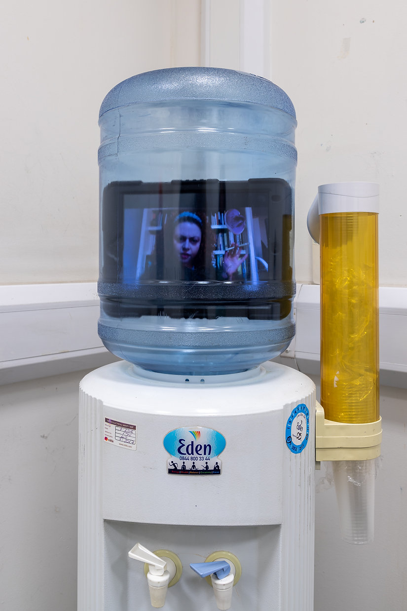 Photo of a watercooler with an Ipad inside, the ipad has a persons face looking perplexed on it, they are holding a pen like a cigarette, with book cases behind them