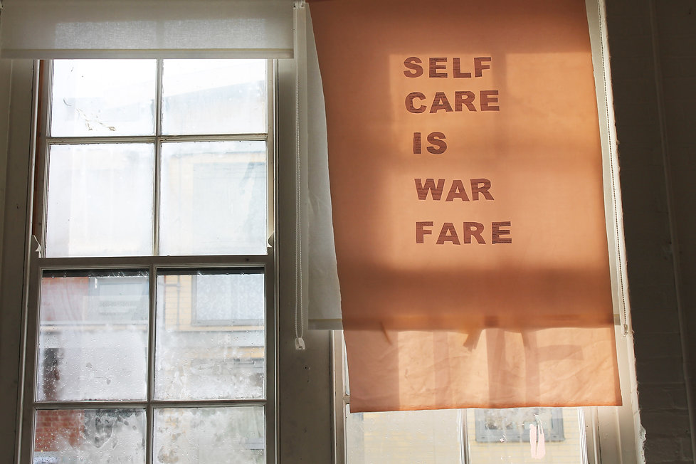 Image Description: A print declaring 'SELF CARE IS WAR FARE' is hung up in front of a window, condensation brewing underneath.