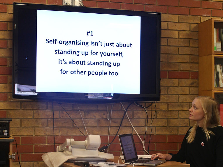 Image Description: A woman looks up at a TV screen mounted on a wall that says '#1 Self-organising isn't justabout standin up for yourself, it's about standing up for other people too.'